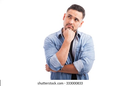 Portrait of a good looking young man looking up and thinking hard against a white background