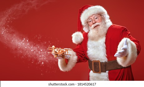 Portrait of the good old Santa Claus with a with a plane on a red background. Merry Christmas and Happy New Year! Copy space.