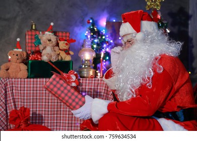 Portrait of good Santa Claus holding a red gift box . Christmas and New Year concept.There is a backdrop that is decorated with the Christmass Festival.
