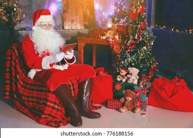 Portrait of good Santa Claus holding a tablet gift  . Christmas and New Year concept.There is a backdrop that is decorated with the Christmas Festival.Vintage color.