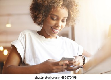 Portrait of good-looking African female student dressed casually holding mobile phone, typing messages, communicating with friends via social networks, using high-Internet connection at cafe