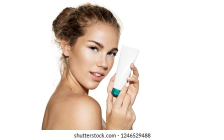 Portrait of good-looking girl holding tube of moisturizer. Lovely young female posing with naked top on white background in studio. Beauty and skincare concept