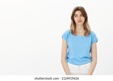 Portrait of good-looking gloomy girlfriend in blue t-shirt, pouting lips and gazing at upper left corner with indifference, having nothing to do, standing bored and confused over gray background