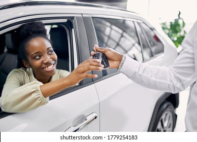 portrait of good-looking lady getting keys by car, woman make purchase in cars showroom. she sits inside of beautiful car and look at sales agent