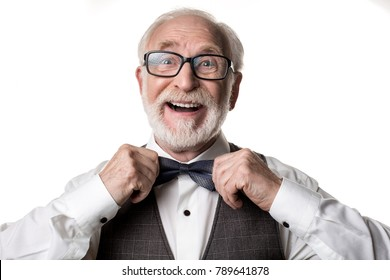Portrait of goodlooking male pensioner standing and fixing his bow tie. Isolated on background