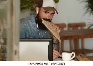 Portrait of good-looking man with beard and tattoo in denim shirt and casual baseball cap watching movie on his laptop in earphones in cafe.