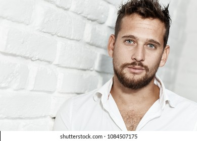 Portrait of goodlooking young caucasian man wearing white shirt standing at wall.