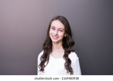 Portrait of good-looking young female kindly smiling. Adorable model with healthy curly hair. Cheerful girl posing for picture on grey background with copy space in left side. Fashion and beauty