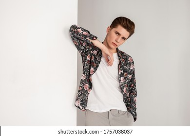 Portrait good-looking young man with serious face with trendy hairstyle in T-shirt in shirt with fashionable vintage floral print near vintage white wall indoors. Modern fashion model guy in room.