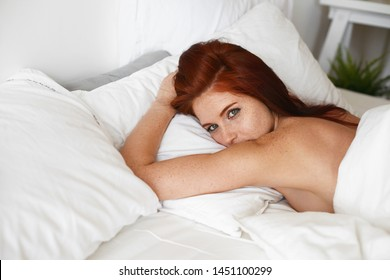 Portrait of gorgeous attractive female with green eyes, ginger loose hair and freckles all over her body lying awake on white bed sheet. Sleepy red haired woman staying in bed on lazy slow morning