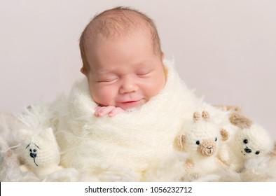 Portrait of gorgeous baby asleep in soft beige wrap