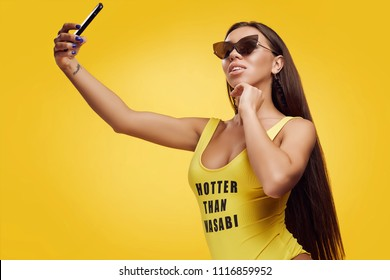 Portrait of gorgeous beautiful sexy brunette with perfect body wearing yellow swimsuit taking selfie on vivid background
