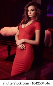 Portrait of gorgeous beauty young brunette woman wearing red dress in luxury interior