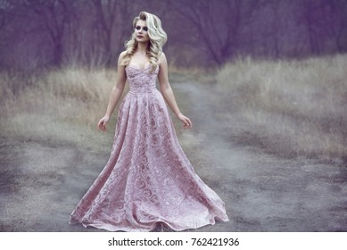 Portrait of gorgeous blond lady with luxuriant hairstyle and beautiful make up wearing luxurious brocade ash rose ball dress walking along the narrow path in the wood. Fairytale concept. Outdoor shot