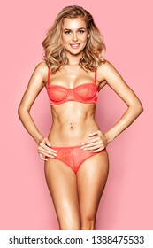 Portrait of gorgeous blonde female wearing red lace bra and pantie. Smiling woman looking at camera with joy and calmness. Beauty concept. Isolated on pink
