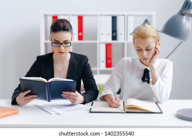 Portrait of gorgeous blonde writing something in big notebook. Concentrated brunette reading book. Thoughtful colleagues working at office together. Way to success concept