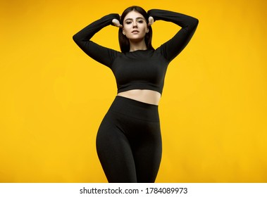 Portrait of a gorgeous body positive Latin woman in a black sports suit posing on a yellow background in the studio