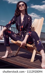 Portrait of a gorgeous bright brunette woman in vivid dress sitting in a wooden chair on the roof of a building