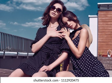 Portrait of a gorgeous bright couple of brunette women in vivid dresses posing on the roof of a building
