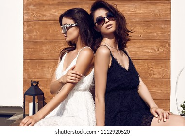 Portrait of a gorgeous bright couple of brunette women in black and white dresses posing on white background