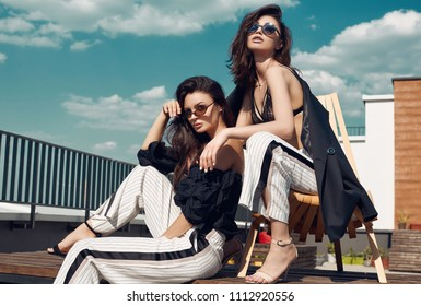 Portrait of a gorgeous bright couple of brunette women in fashion dresses posing on the roof of a building with vivid sky