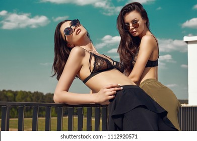 Portrait of a gorgeous bright couple of brunette women in bra posing on the roof of a building