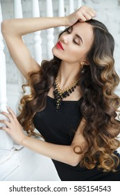 Portrait of a gorgeous brunette with chic curls in a little black dress on a bright terrace.