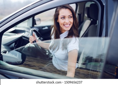 Portrait of gorgeous brunette in shirt entering her car. With one hand woman is holding steering wheel and with other shutting door.