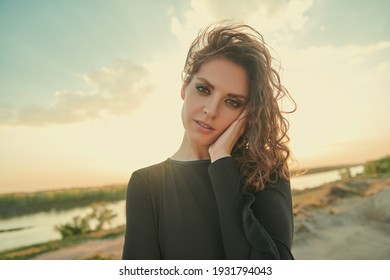 Portrait of a gorgeous brunette woman against the backdrop of a landscape with sands and a river. Beauty, make-up.