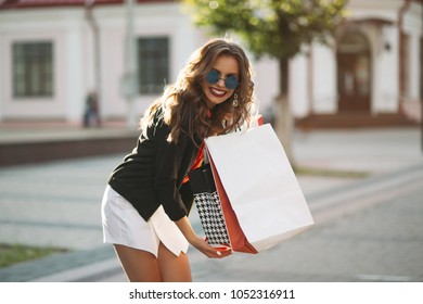 Portrait of gorgeous brunette woman with hairstyle, wearing sunglasses, jacket and mini skirt holding many shopping bags and smiling at camera in the street on sunny day.