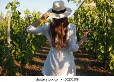 Porträt einer wunderschönen Brunette Frau, die sich in den Weinbergen amüsiert.