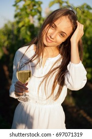 Portrait of a gorgeous brunette woman having wine fun in the vineyards.