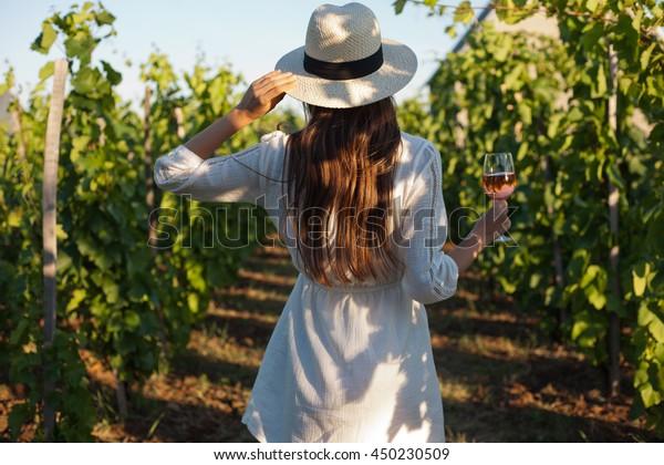 ぶどう園でワインを楽しむ豪華なブルネット女性のポートレート。