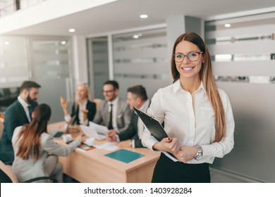 Portrait of gorgeous businesswoman in formal wear, with long brown hair and eyeglasses holding clipboard while standing at board room. Strive for progress, not perfection.