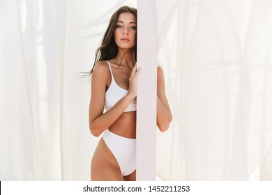 Portrait of gorgeous caucasian woman in swimsuit standing over white curtains at beach summer resort