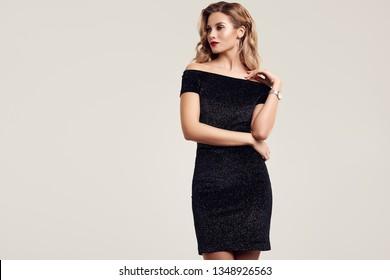 Portrait of gorgeous elegant sensual blonde woman wearing fashion black dress isolated on white background