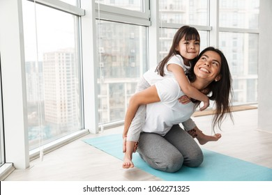 Portrait of gorgeous family mother and child having fun and giving piggyback while doing sports exercises on yoga mat at home