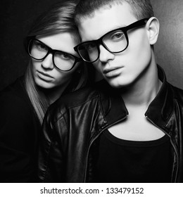 Portrait of gorgeous fashion twins in black clothes wearing trendy glasses and posing over gray background together. Hipster style. Black and white (monochrome) studio shot.