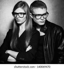 Portrait of gorgeous fashion twins in black clothes wearing trendy glasses and posing over metal background together. Perfect hair and skin. Natural make-up. Hipster style. Black and white studio shot