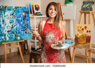 Portrait of a gorgeous female artist working on several art projects on her studio