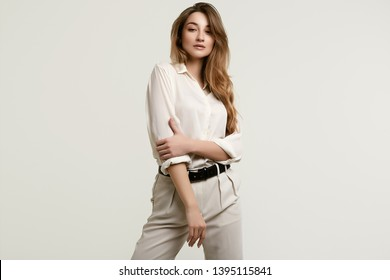 Portrait of gorgeous female brunette model posing in white fashion clothes in studio
