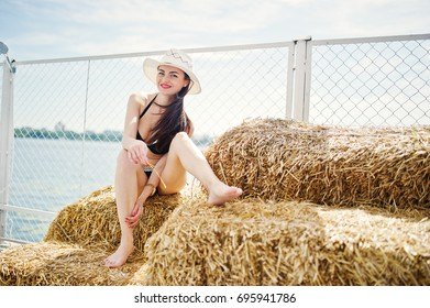 Portrait of a gorgeous girl in black bikini swimsuit posing on the hay bale with a hat by the lake.