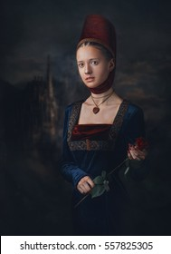 Portrait of a gorgeous girl in medieval era dress and headdress. Medallion in a shape of heart. Holding red rose in hands