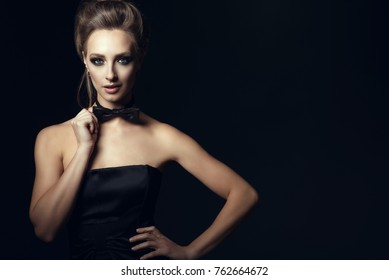 Portrait of gorgeous glam woman with beautiful make up and updo hair wearing black corset dress touching bow tie on her neck. Isolated on black background. Gamble and party concept. Copy-space