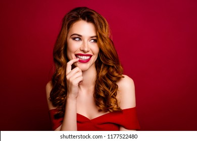 Portrait of gorgeous, good-looking, alluring woman with modern curly hairstyle look aside holds a finger near the lips isolated on dark red background