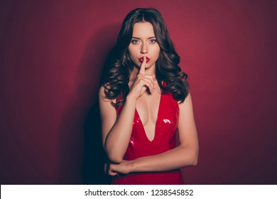 Portrait of gorgeous graceful pretty dreamy brunette with modern curly hairstyle she stand in her lustrous shine mini wear isolated on deep red background hold forefinger finger on lips