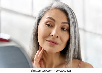 Portrait of gorgeous happy middle aged mature asian woman, senior older 50s lady pampering touching face looking at herself at mirror indoors. Ads of lifting anti wrinkle skin hair care spa.