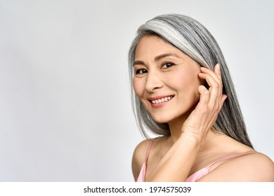 Portrait of gorgeous happy middle aged mature asian woman, senior older 50 year lady looking at camera touching her face isolated on white. Ads of lifting anti wrinkle skin care, spa. Copy space.