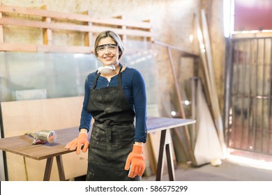 Portrait of a gorgeous Hispanic female carpenter working in a woodshop and smiling