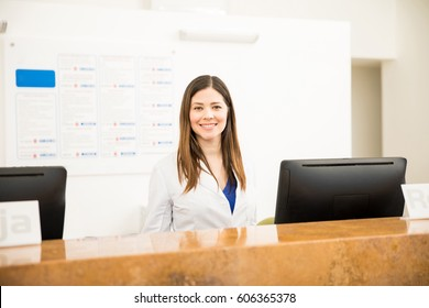 Portrait of a gorgeous Hispanic receptionist working in a health clinic and smiling